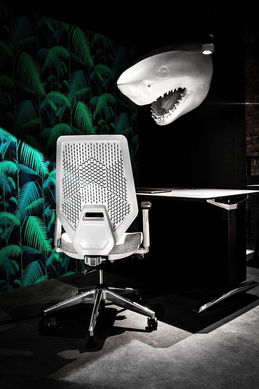 biały fotel obrotowy przy biurku na tle głowy rekina