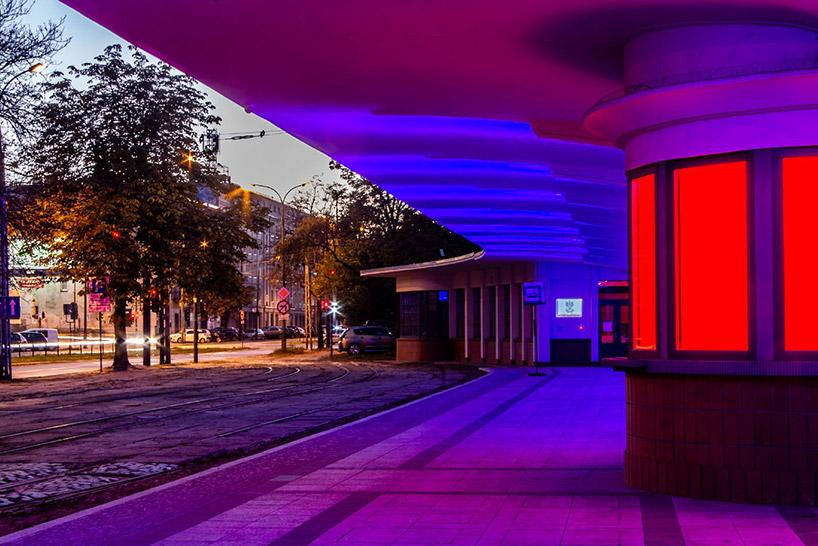 iluminacja budynku zdługim zadaszeniem wfioletowo-czerwonych kolorach