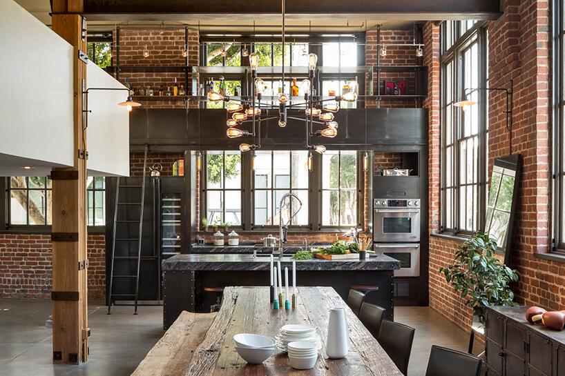 ciemna industrialna kuchnia połączona zjadalnią na tle ceglanej ściany
