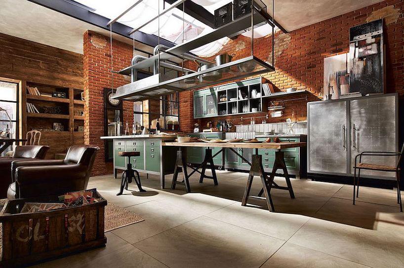 industrialna kuchnia zzielonymi szafkami zwyspą istołem na metalowych przemysłowych nogach zdrewnianym blatem na tle ceglanych ścian