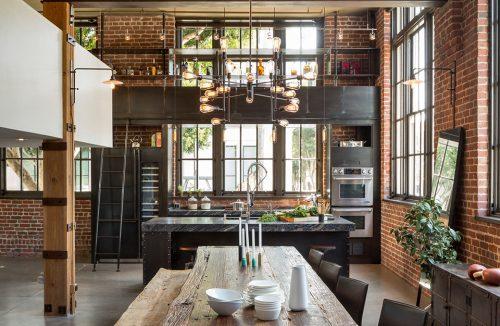 ciemna industrialna kuchnia połączona z jadalnią na tle ceglanej ściany