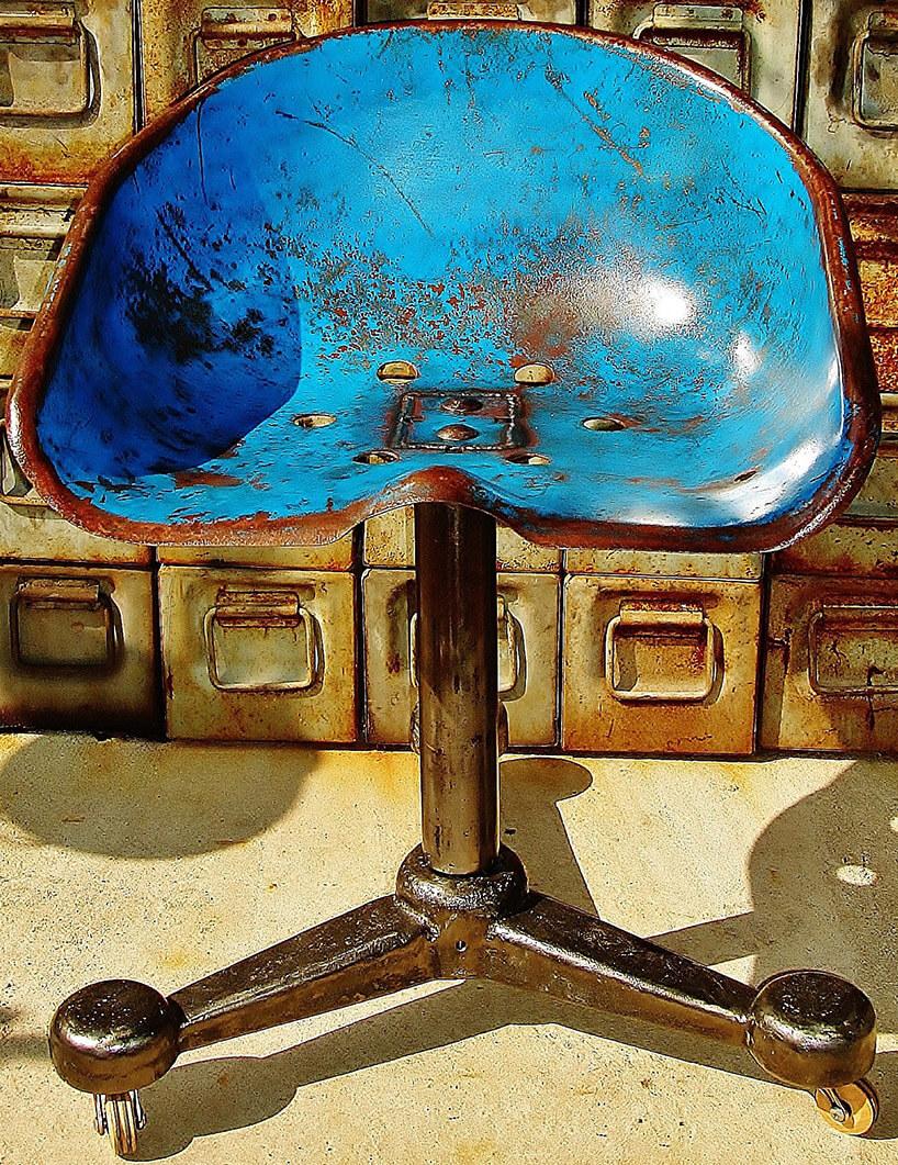 niebieskie siedzisko na kółkach ze starej maszyny rolniczej