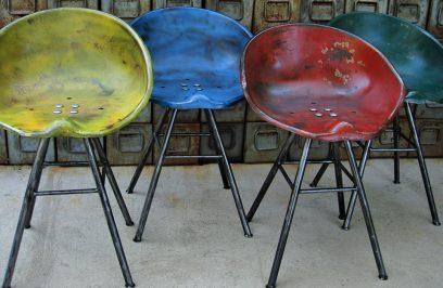 cztery różnokolorowe stołki z siedziskami ze starej maszyny rolniczej
