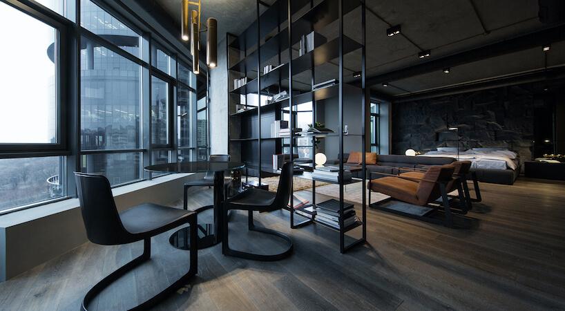 elegancki ciemny salon błyszczącym stołem ztrzema czarnymi krzesłami na tle okien