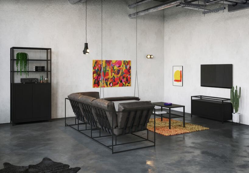 industrialne wnętrze zbiałymi ścianami iszarą betonową podłogą zzczarną sofą isiedziskiem podwieszonym na łańcuchach