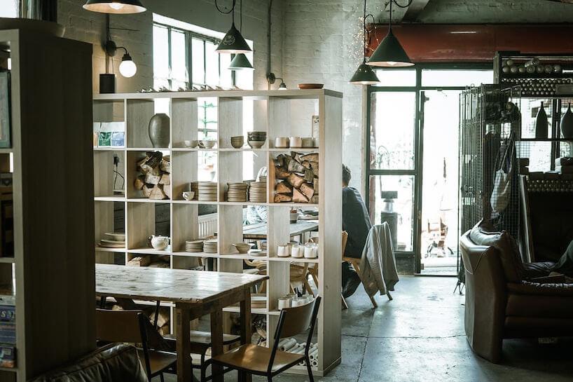 industrialne wnętrze restauracji ze starym stołem iszkolnymi krzesłami pod industrialnymi lampami