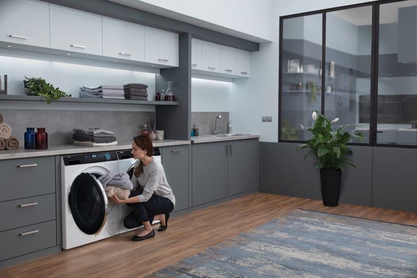 dwie nowoczesne białe pralki Haier zczarnymi drzwiczkami wszarej zabudowie podczas uruchamia