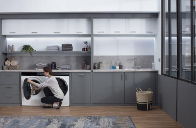 kobieta wrzucająca ubrania do pralki w pokoju gospodarczym