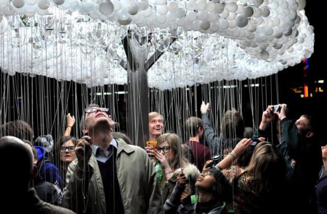 ludzie pod instalacją z żarówek