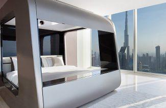 zabudowane srebrne łóżko na tle widoku z apartamentowca