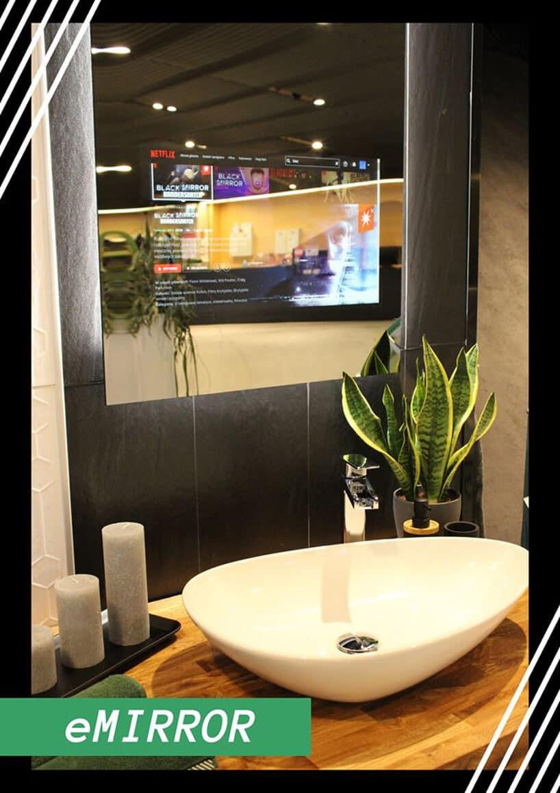 interaktywne lustro eMIRROR na czarnych kafelkach waranżacji łazienki zdrewnianym blatem pod białą umywalką