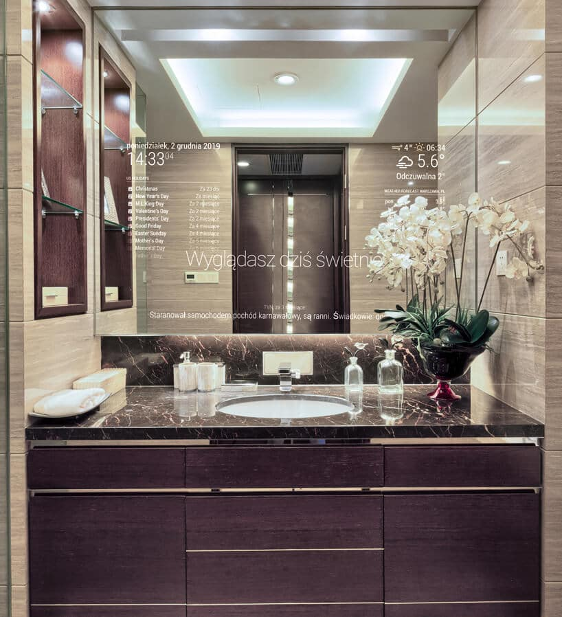 inteligentne lustro od Mirror Investment waranżacji łazienki zciemną szafką ijasno brązowymi kafelkami