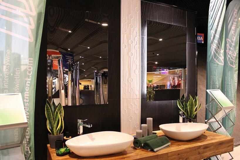 dwa interaktywne lustra eMIRROR na czarnych kafelkach waranżacji łazienki zdrewnianym blatem pod białą umywalką