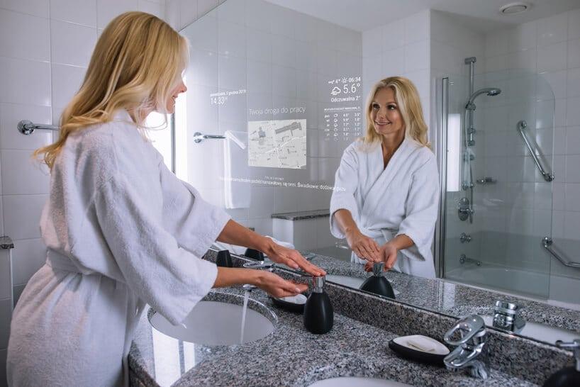 kobieta wbiałym szlafroku weleganckiej łazience zinteraktywnym lustrem od Mirror Investment