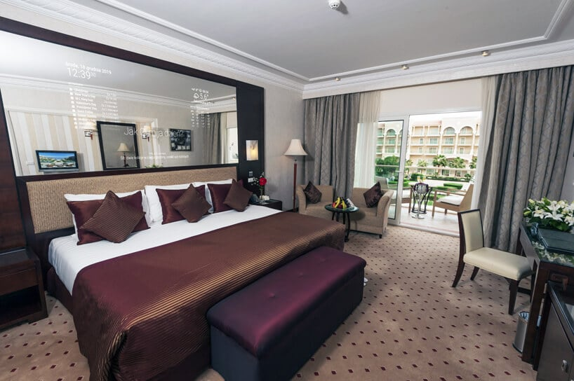 duże interaktywne inteligentne lustro od Mirror Investment weleganckim pokoju hotelowym nad dużym łóżkiem