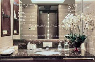 inteligentne lustro od Mirror Investment w aranżacji łazienki z ciemną szafką i jasno brązowymi kafelkami