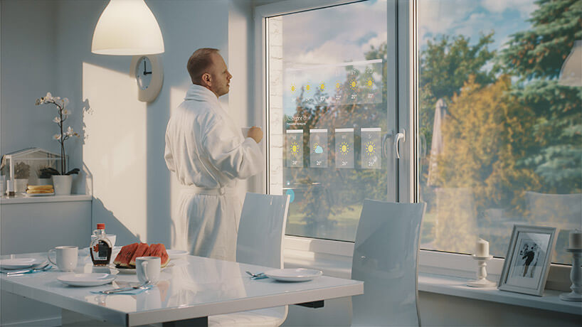 mężczyzna wszlafroku stojący przed oknem zekranem LCD