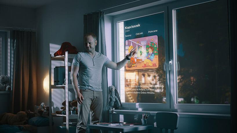 mężczyzna stojący przy oknie zmatrycą LCD