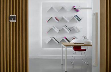 nowoczesne białe wnętrze małe biurko z czerwony krzesłem na tle ściany z trójkątnymi półkami na książki z panelem sterującym ABB na drewnianej ścianie