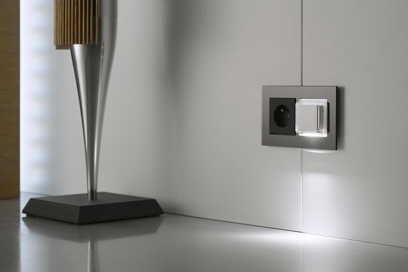 szare gniazdko zbiałym modułem domu inteligentnego od ABB obok lampy podłogowej zczarną podstawą