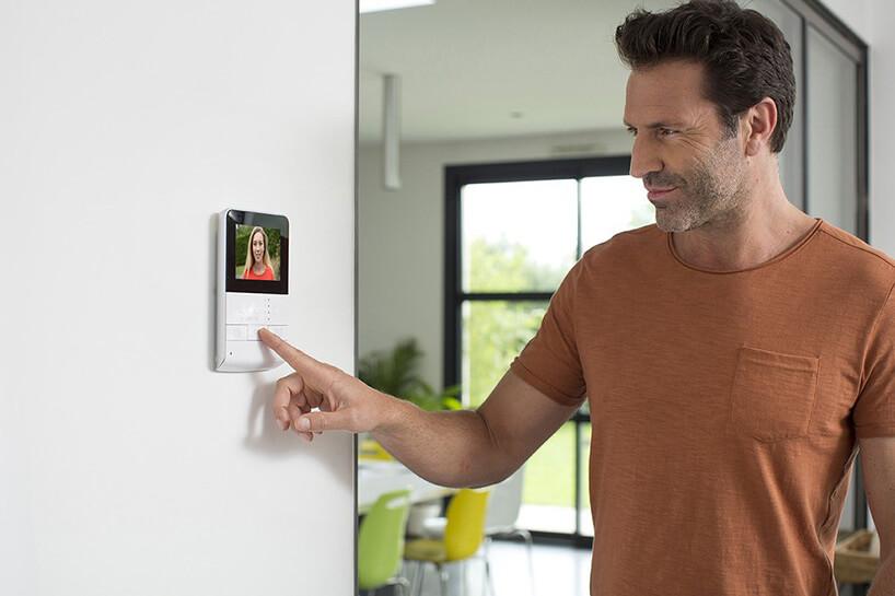 biały ekran wideodomofonu na białej ścianie mężczyzna wpomarańczowym podkoszulku
