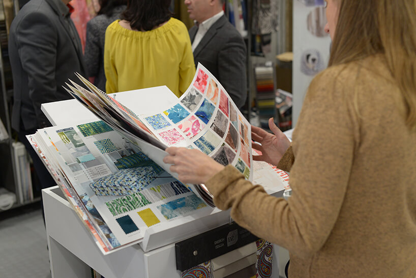 kobieta przeglądająca katalog próbek zmateriałami obiciowymi