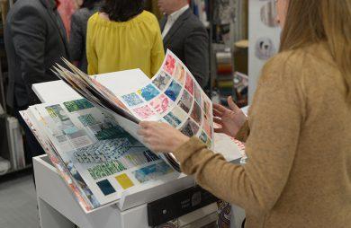 kobieta przeglądająca katalog próbek z materiałami obiciowymi