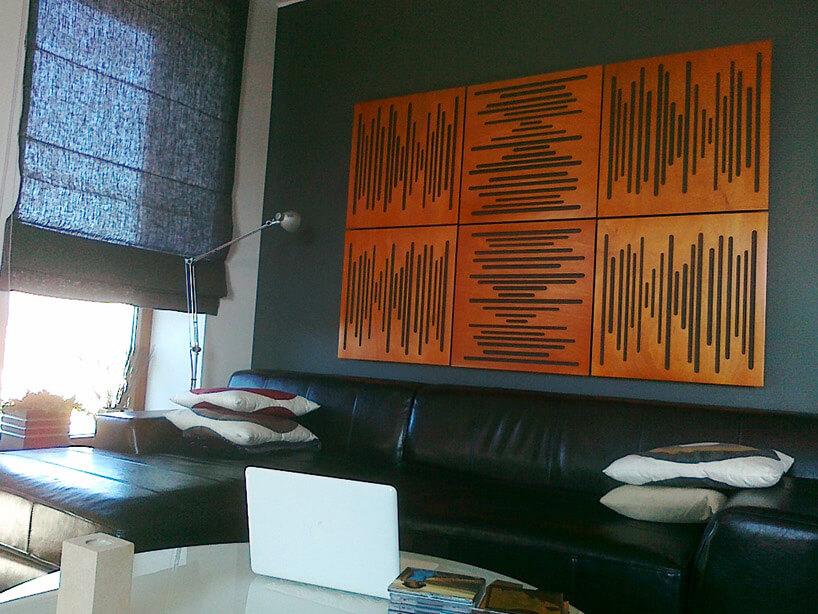 czarna sofa wsalonie na tle ściany zbrązowymi panelami