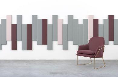 pojedynczy fotel na tle ściany z kawałkami filców