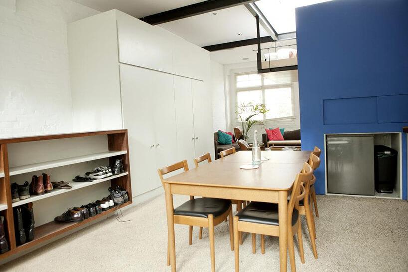 drewniany stół wjadalni obok niebieskiej ściany