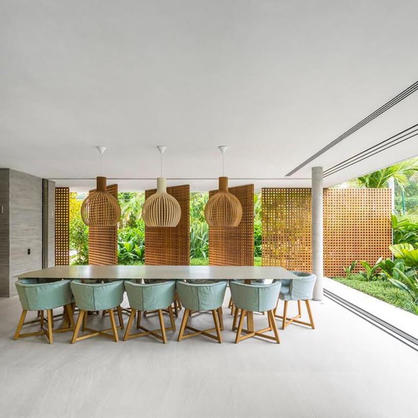jadalnia otwarta na ogród zdużym stołem izielonkawymi niskim krzesłami