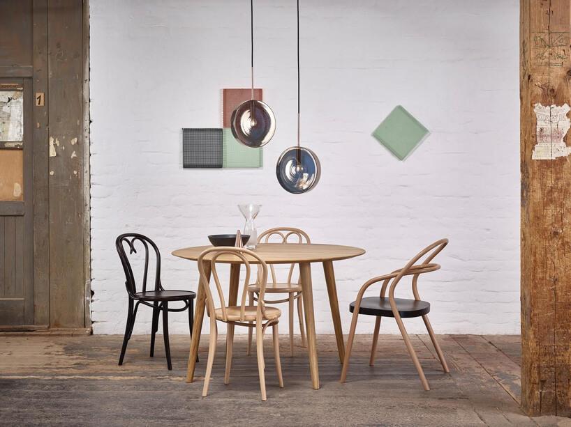 okrągły stolik zczterema krzesłami pod dwoma lampami ze srebrnym kloszem