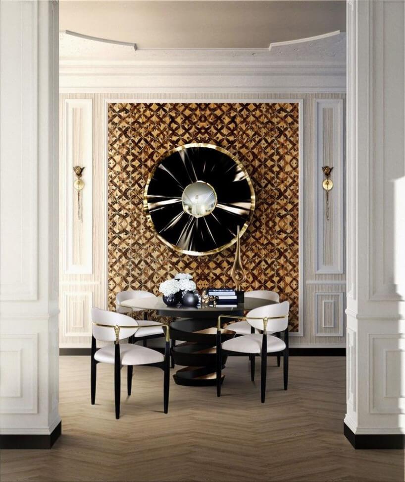 okrągły ciemny stół zbiało-brązowymi fotelami na tle ściany zdużą czarną ozdobą na ścianie