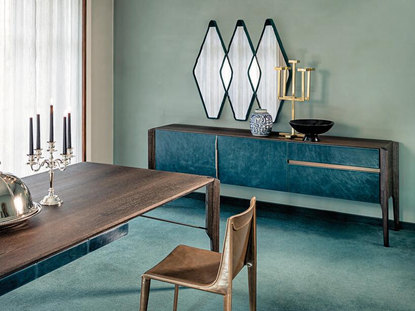 jadalnia wturkusowym kolorze zbrązowym drewnianym stołem ze świecznikiem inakrytą tacą