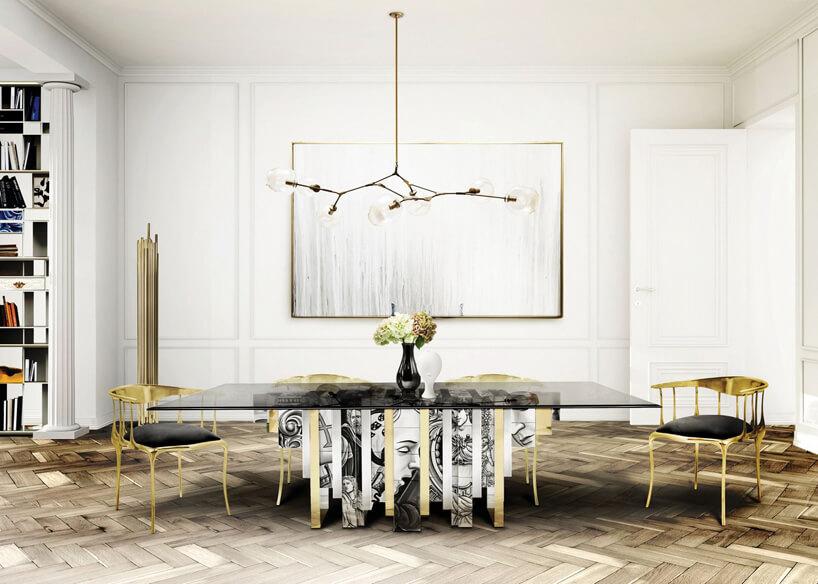 biała jadalnia glamour ze stołem ze szklanym ciemnym blatem idwoma złotymi krzesłami
