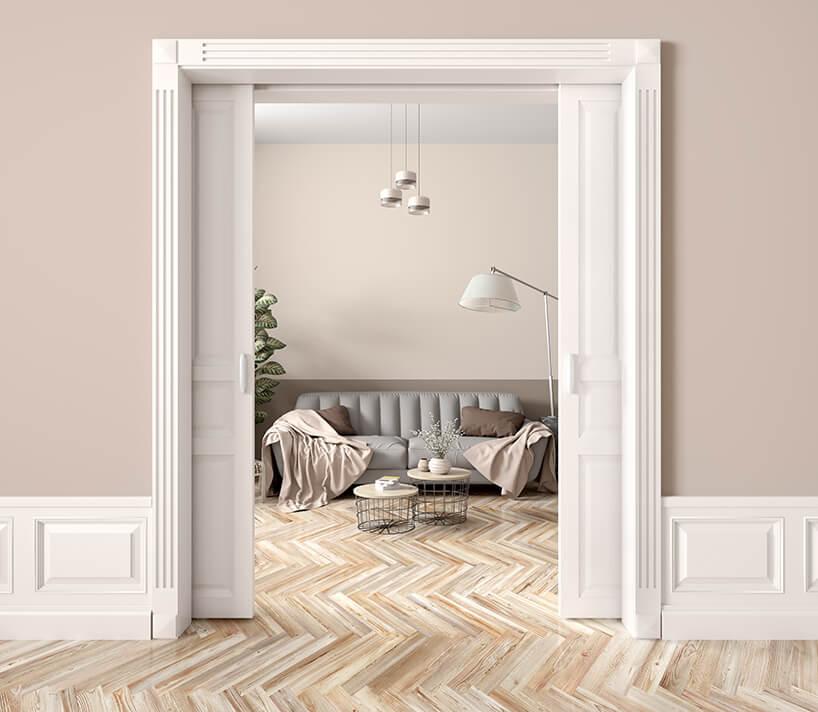 elegancke dwu skrzydłowe drzwi przesuwne wbeżowe ścianie na tle szarej sofy wsalonie
