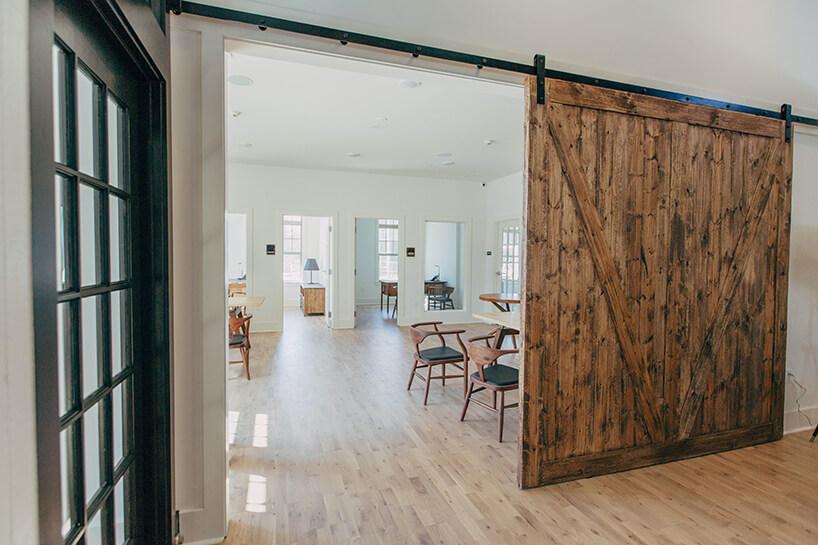 masywne surowe drewniane drzwi przesuwne na czarnej metalowej szynie