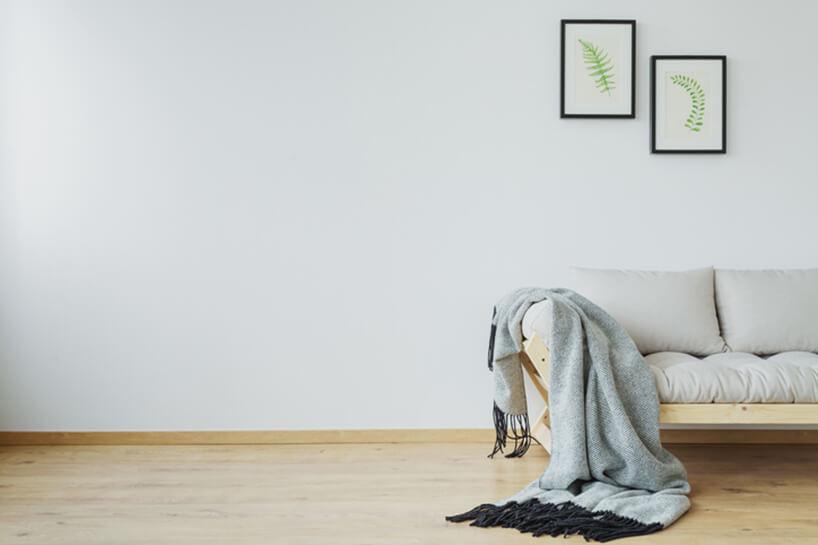 sofa zdrewnianym stelażem iszarymi poduszkami na jasnej drewnianej podłodze