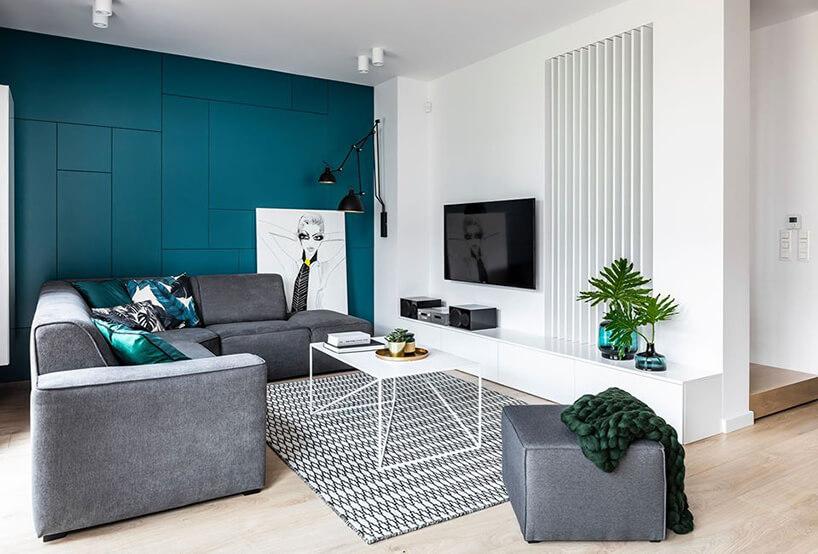 biały salon zjedną mocno zieloną ścianą jako tło szarej narożnej sofy