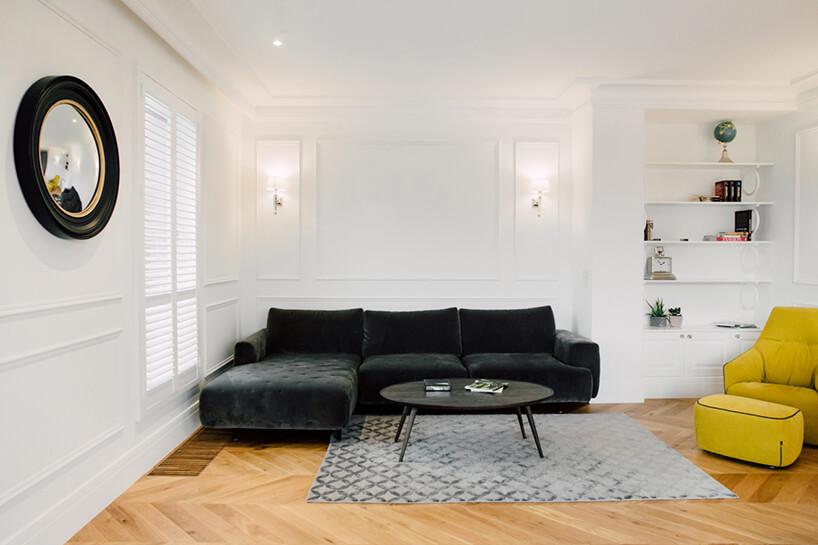 biały salon ze sztukaterią na ścianach jako tło dla ciemnej sofy