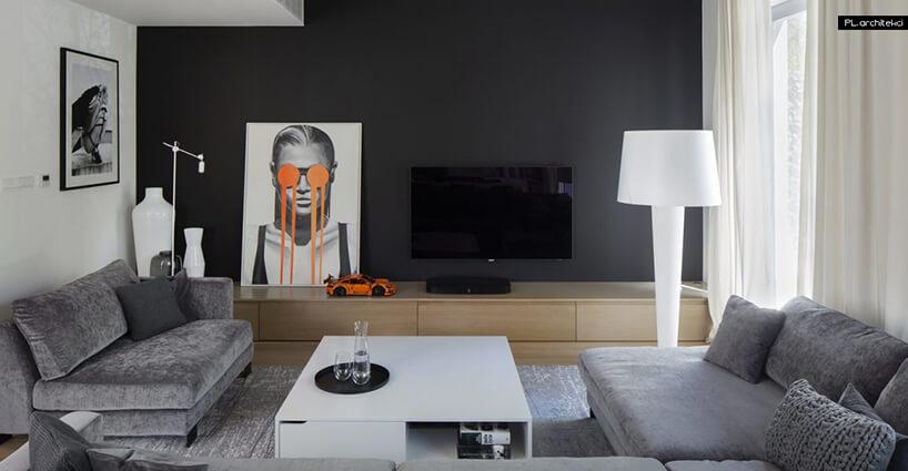 elegancki salon zszarumi sofami długą szafką drewnianą na tle czarnej ściany ztelewizorem