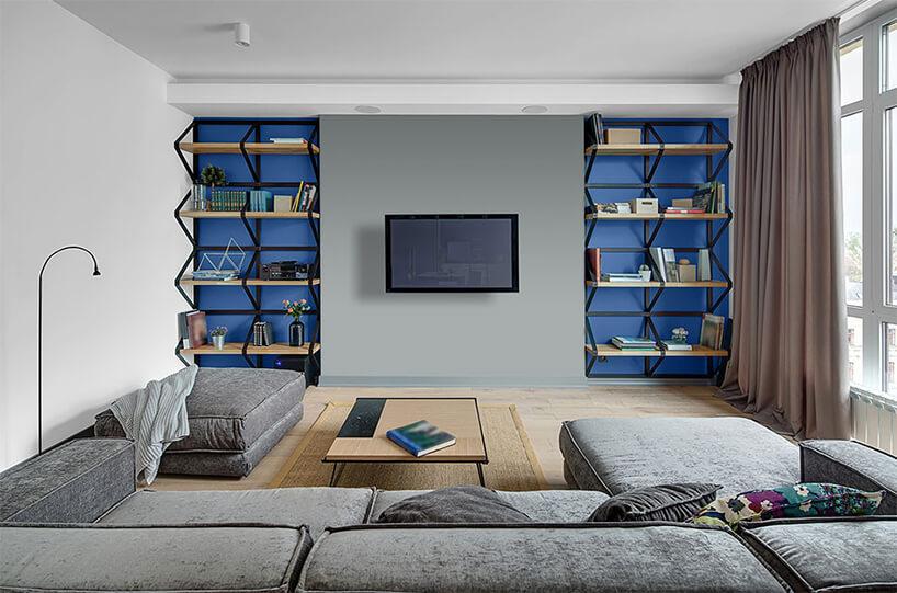 dwie niebieskie wnęki zpółkami wszarej ścianie ztelewizorem