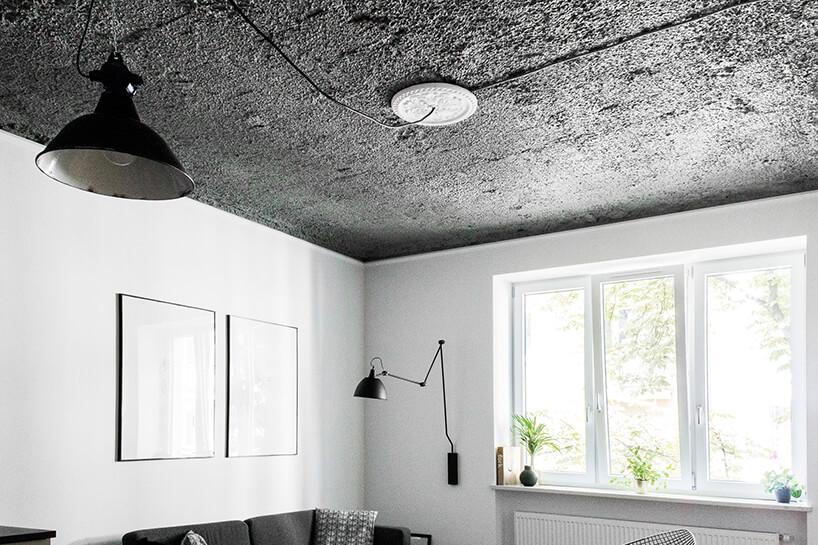 czarny sufit na nieruwnej strukturze wbiałym salonie