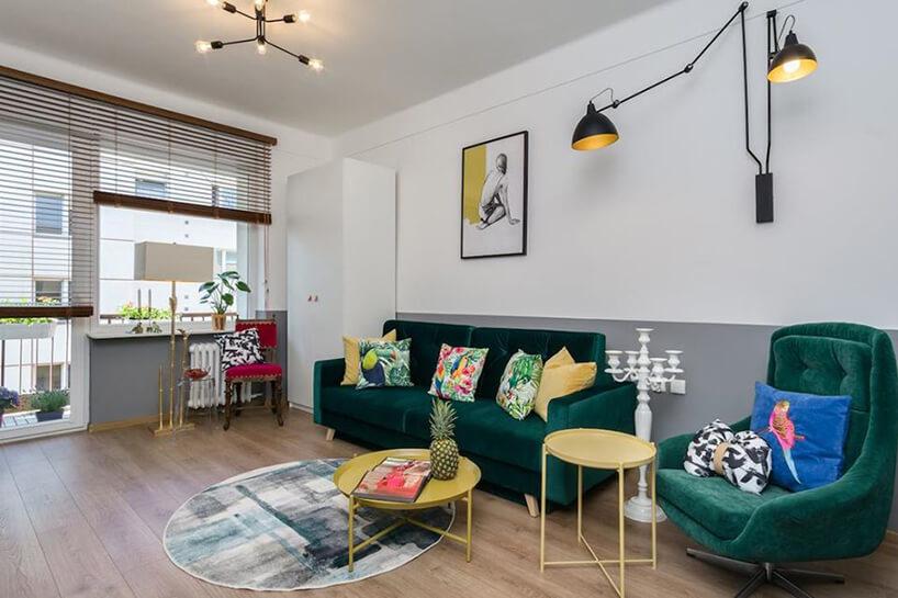 jasny salon zodciętym na szaro dołem ścian jako tło dla zielonej sofy ifotela