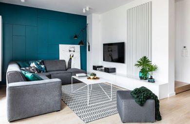 biały salon z jedną mocno zieloną ścianą jako tło szarej narożnej sofy