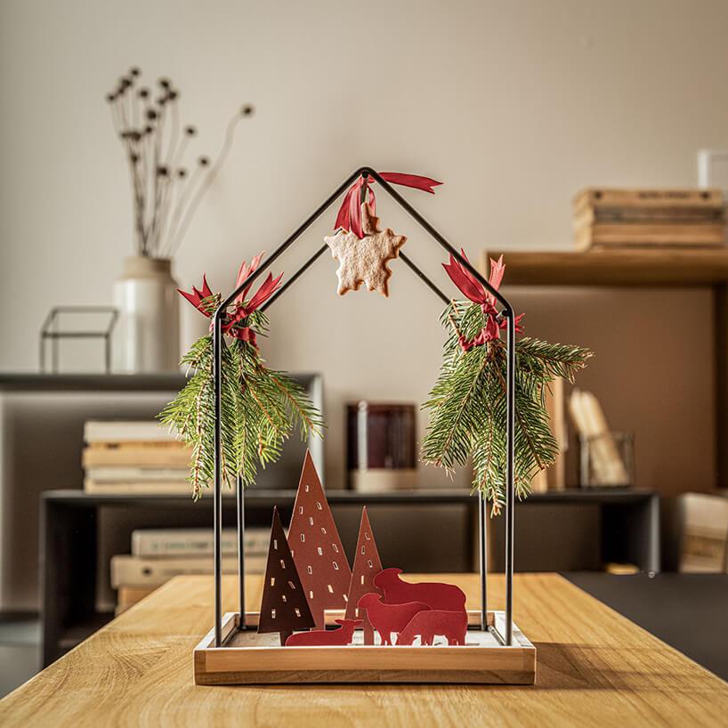 wyjątkowa metalowa konstrukcja wkształcie domu zdrewnianą podstawą na drewnianym stole od VOX