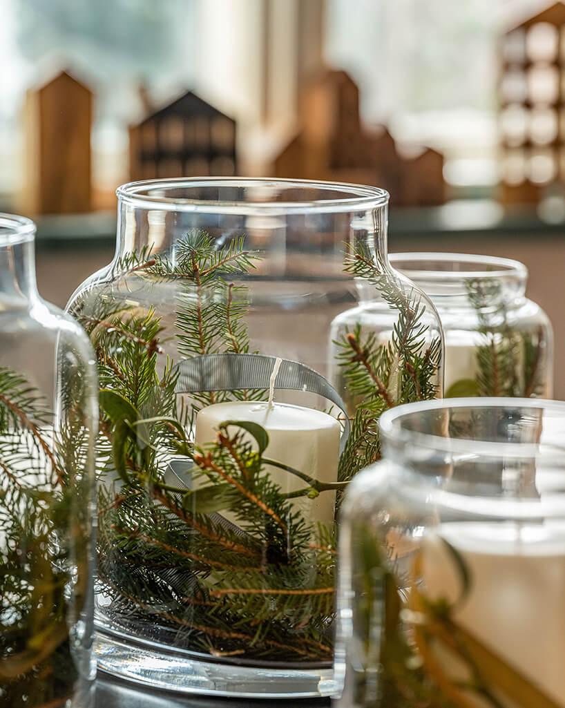eleganckie szklane słoje zwłożonymi gałązkami iglastymi ijemiołą wokół świec od VOX
