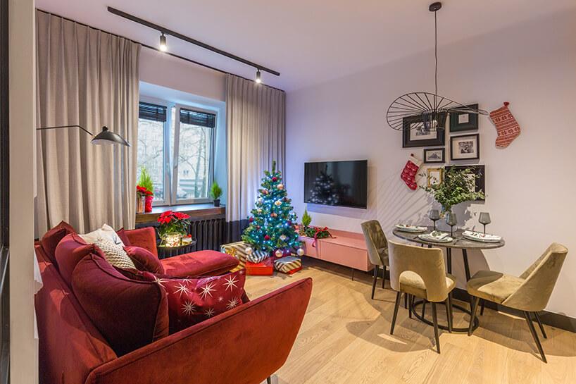 aranżacja jasnego salonu zdrewnianą podłogą zczerwoną sofą od Decoroom