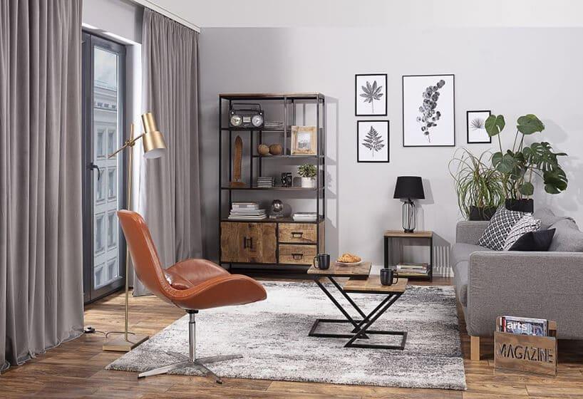 rudawy fotel skórzany obrotowy na metalowej nodze na szarym dywanie typu shagy wszarym pomieszczeniu zszarymi ścianami