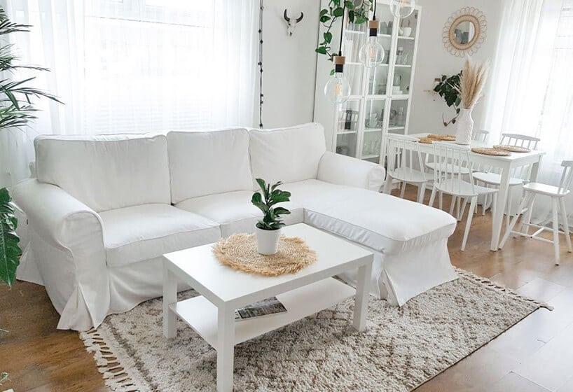 biała kanapa wliterę Lstojąca wraz zbiałym stołem na dywanie zfrędzlami wsalonie zbiałym stołem ikrzesłami